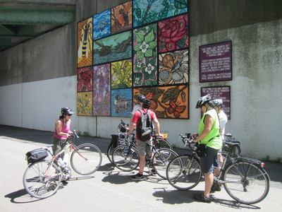 Cyclists admire mural along the Neponset Trail